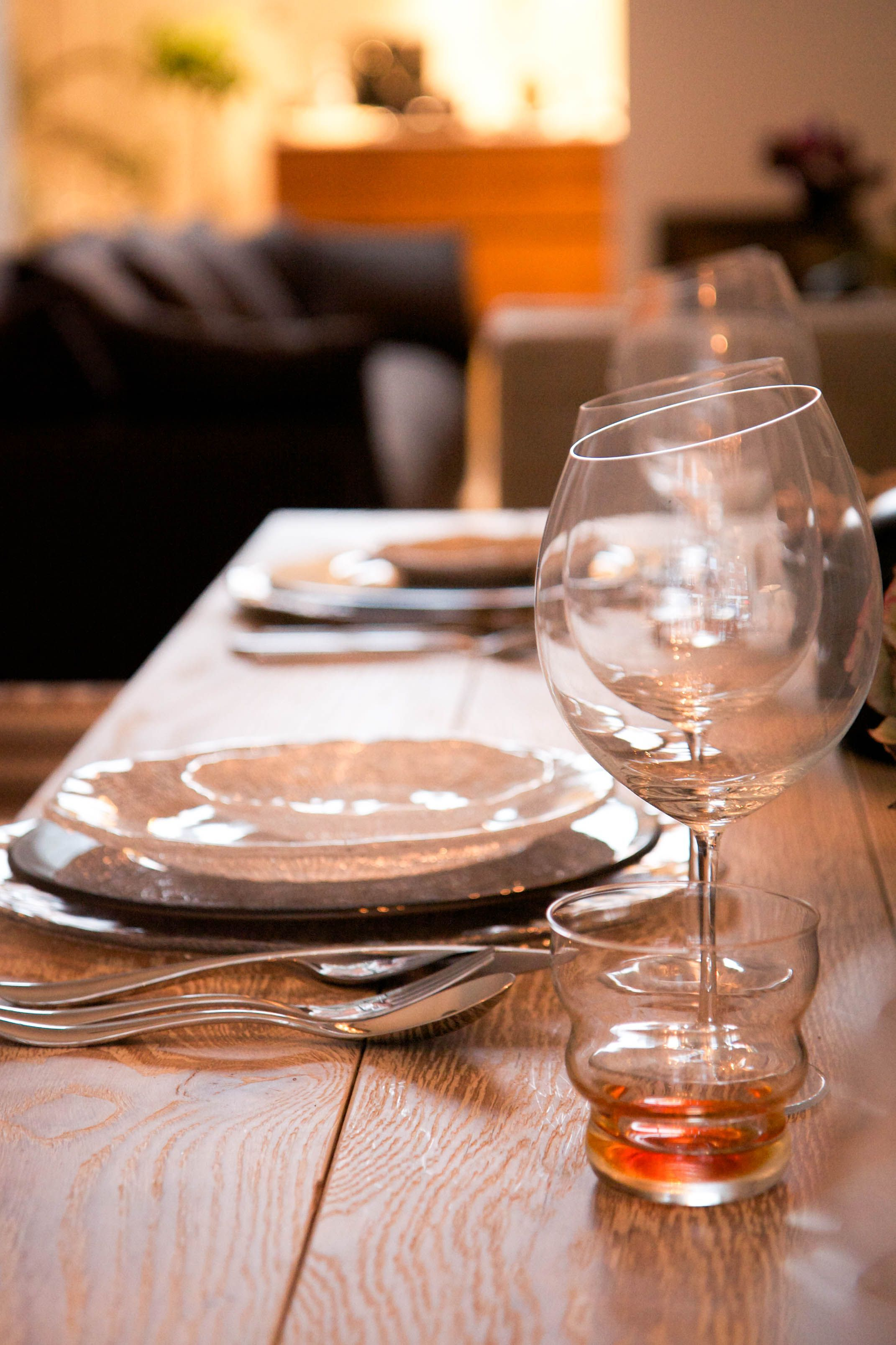 A dinner table with multiple glass plates and wine glasses.