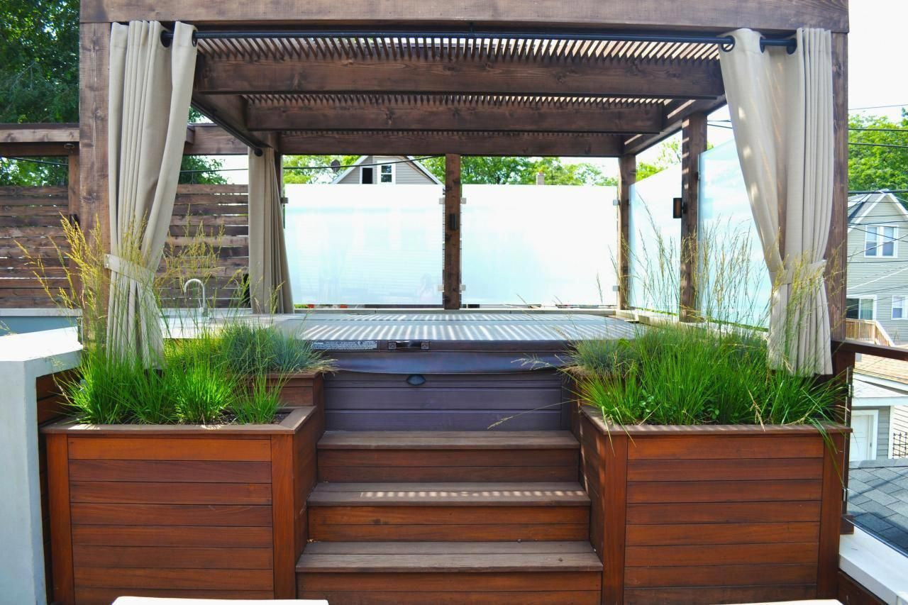 The Bucktown Hot Tub Retreat provides a serene space to relax amid the active city. The space features a new roof deck with Ipe decking, concrete counters, cedar pergola, tempered glass panels and fire pit. Additional features include seating around the fire pit, sun loungers, bar area and outdoor refrigerator/freezer. #pergolaDeck #hottubdeck