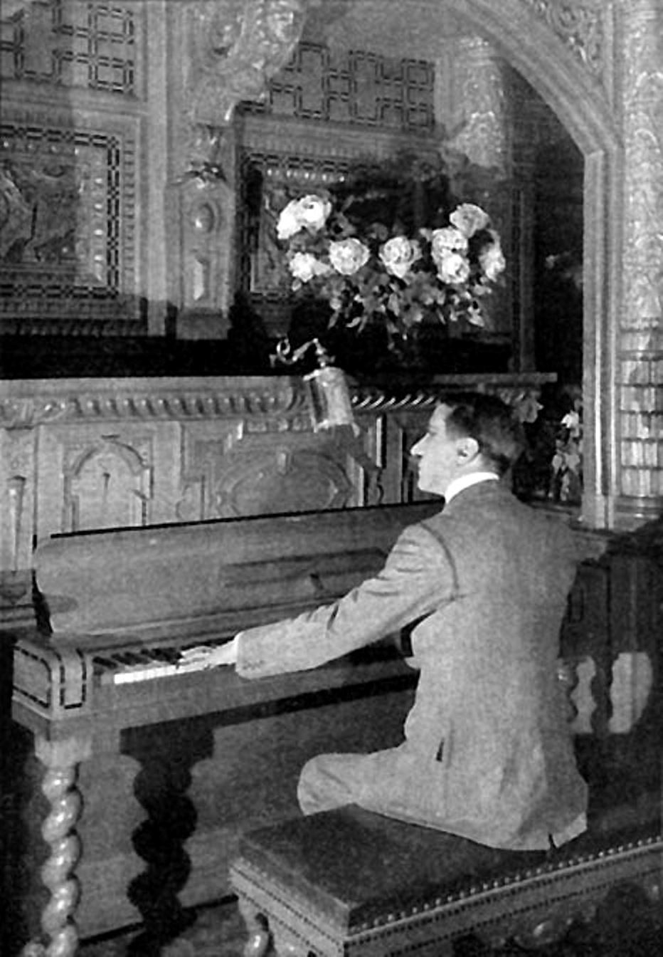 a man playing the piano on the first class dining room ...