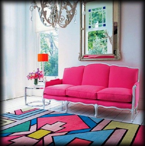 Sala com sofá pink e tapete colorido.
