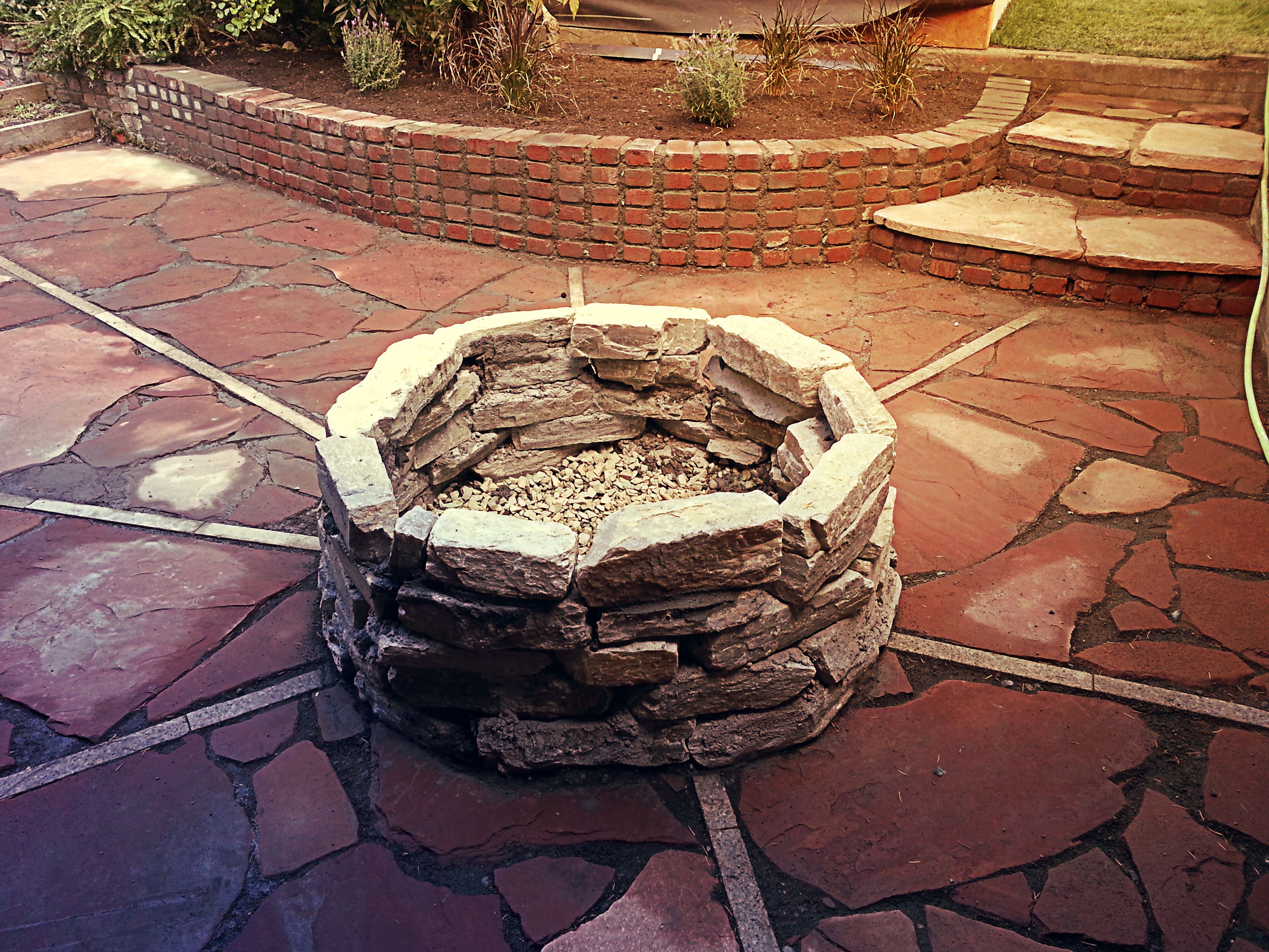 a new rustic patio and natural firepit designed by ecogreen