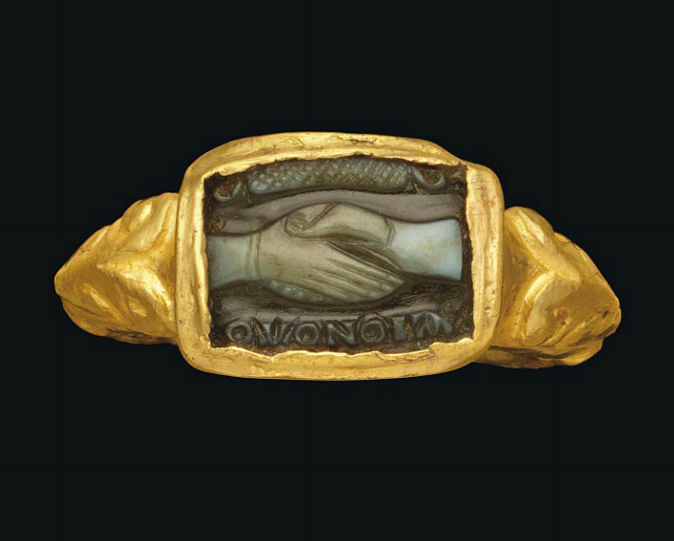 A BYZANTINE GOLD AND AGATE CAMEO RING   CIRCA 5TH CENTURY A.D.   The hollow gold hoop with scrolling foliate shoulders, with raised rectangular bezel, the cameo carved in two layers, white on black, with clasped right hands (dextrarum iunctio), the female hand on left wearing bracelet, a Greek inscription below reading, 'Concord', a garland above  1 in. (2.5 cm.) wide