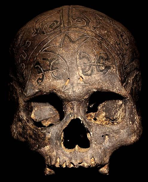DAYAK TRIBE: HEAD HUNTING HUMAN TROPHY SKULL #16  HAND CARVED HUMAN SKULL.  THE DAYAK TRIBE, FROM BORNEO ISLAND  INDONESIA, CARVE DESIGNS INTO THE SKULLS  OF THEIR HEADHUNTED VICTIMS AND INSERT WOODEN FIGURES.