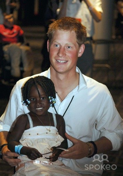 Prince Harry holds 3 year old Eufrafina (the daughter of Sandra Tagica who met Princess Diana in Angola in January 1997)at a lunch party at Wembley Stadium