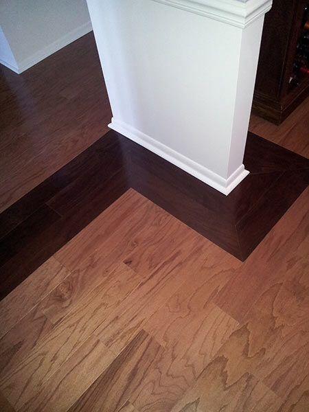 Dark hardwood floor borders a medium light hardwood floor for an