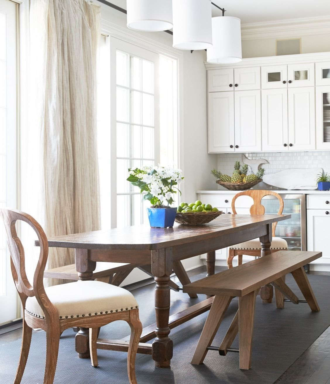 All white kitchen with farm table dining bench