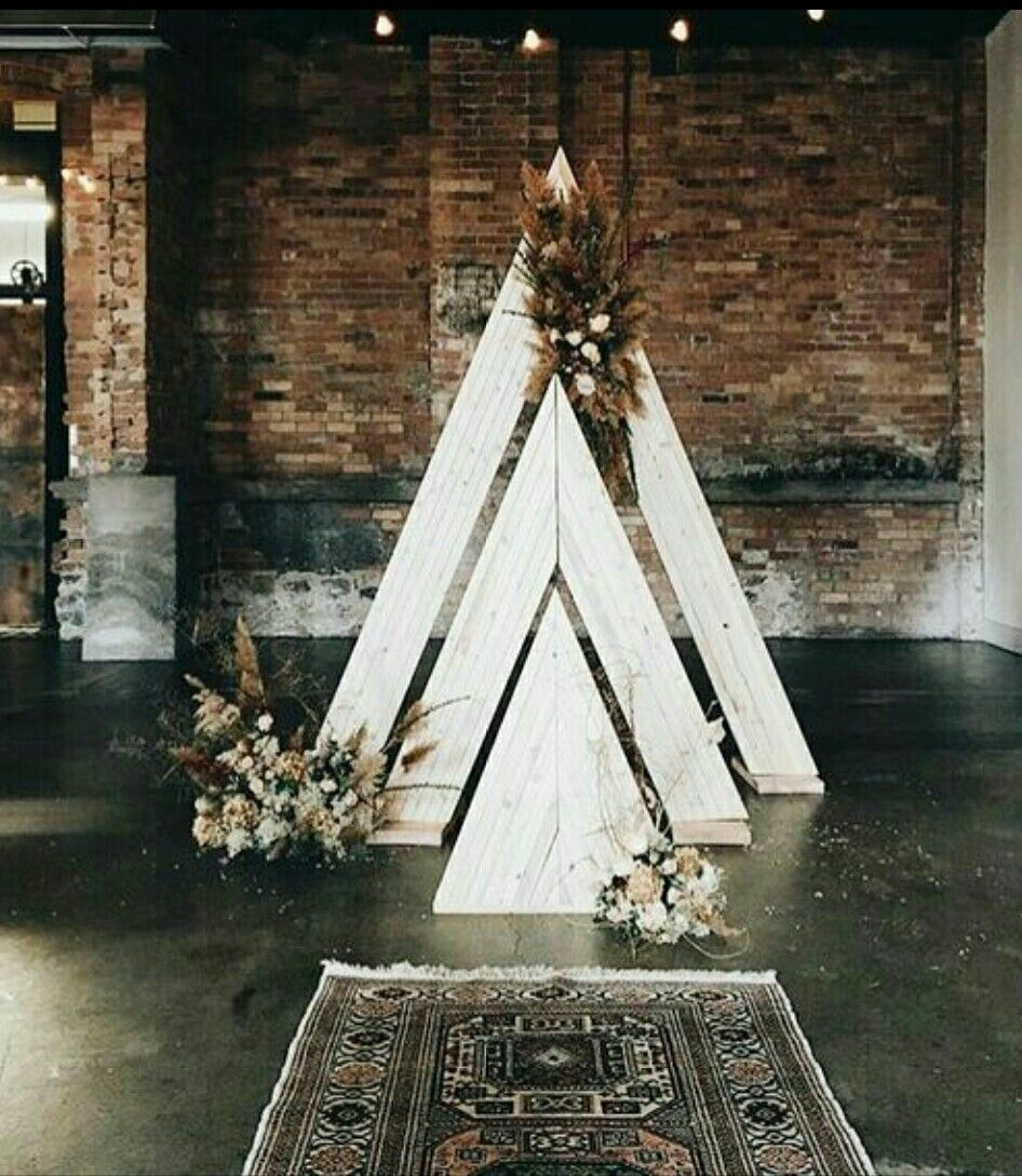 White Triangular Boho Wedding Arch With A Vintage Rug