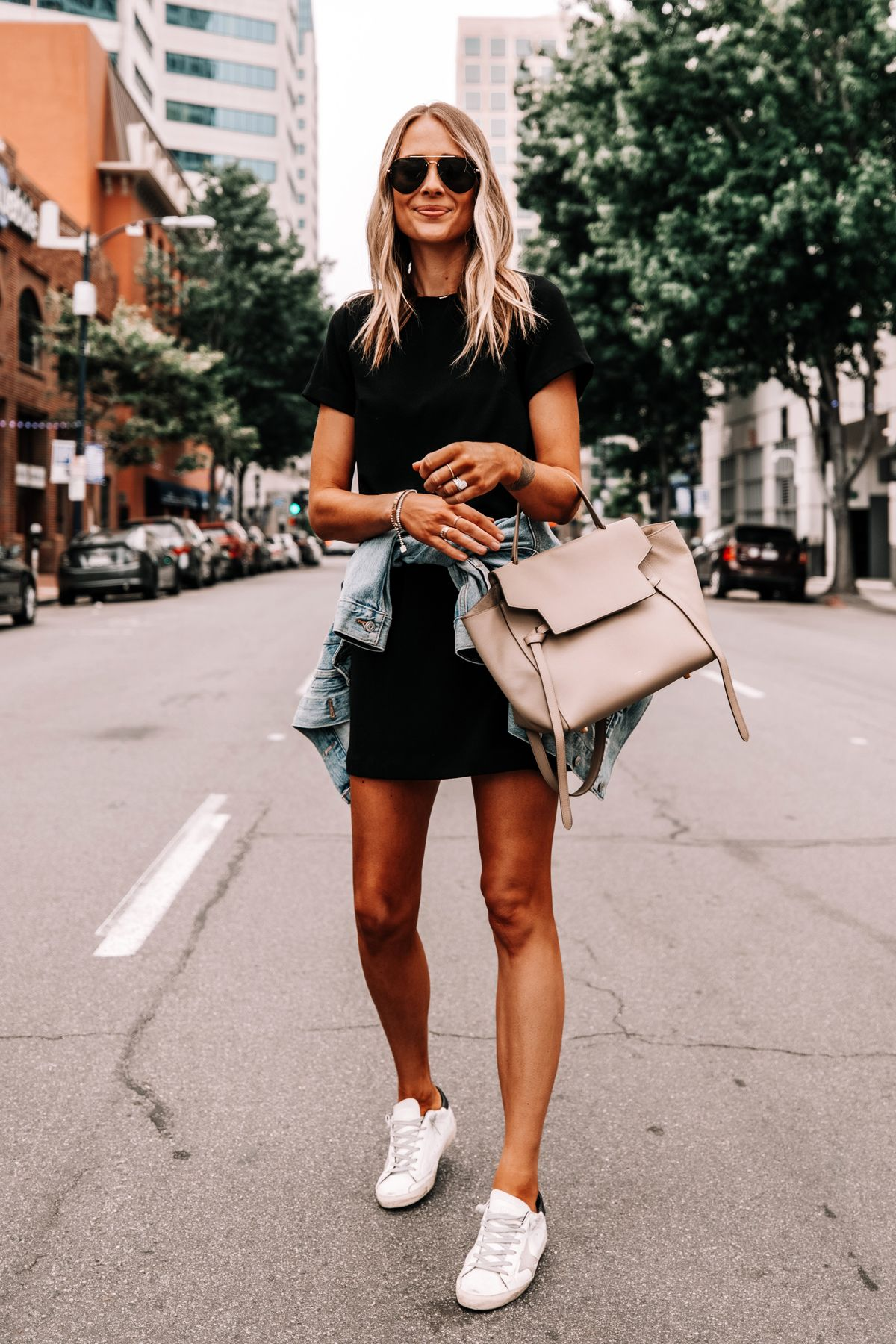 Fashion Jackson Wearing Black Dress Denim Jacket Golden Goose Sneakers Celine Belt Bag Street St Fashion Jackson Dress And Sneakers Outfit Summer Dress Outfits [ 1800 x 1200 Pixel ]