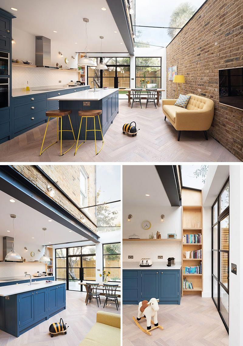 This modern extension is open plan with a new dark blue kitchen, a pastel yellow sofa that sits against a brick wall, and a dining area that has views of the backyard through the black-framed windows and doors. A skylight running the length of the extension adds an abundance of natural light to the space. #ModernHouseExtension #HouseExtension #BlueKitchen #Skylight #kitchendiners