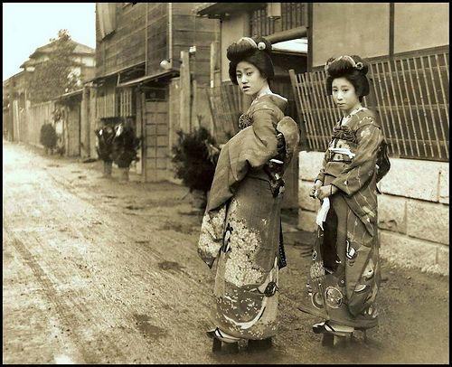 """DRESSED FOR THE OCCASION -- Two Girls in Gorgeous Garb and Geta in OLD JAPAN by Okinawa Soba, via Flickr.  The above ca.1915-23 silver print is true """"street photography"""" on a rainy day...on a muddy road... on the way to some festive occasion, or possibly a New Years Party where these young Geisha are called for.    Their faces a tad bit of impatience, only politely stopping to accommodate Enami's request for a photo."""