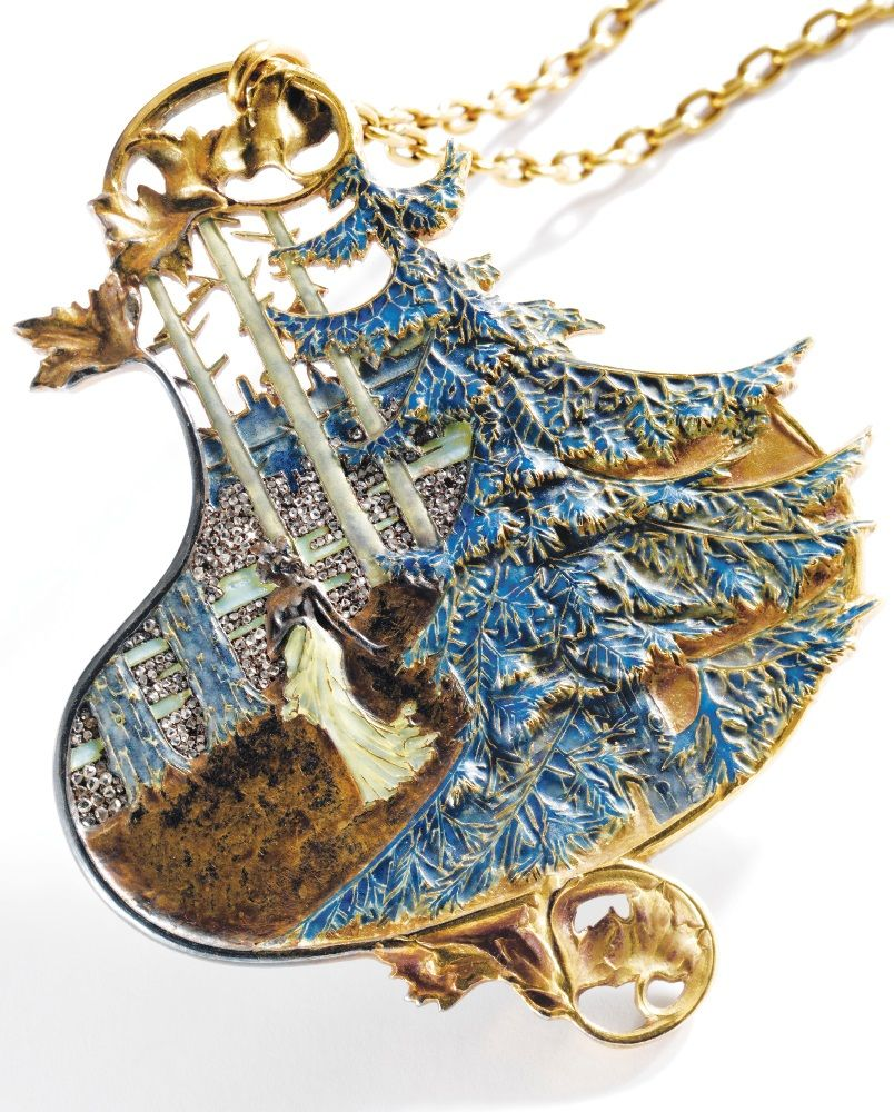 René Lalique - An Art Nouveau Gold, Diamond and Enamel Landscape Pendant, Circa 1898-1900. The pendant designed as a partially clad woman in diaphanous drapery strolling through a forested landscape, against a sky of sparkling diamonds, with leafy flourishes above and below, variously applied with blue and pale green enamel accents and small rose-cut diamonds, the back of the pendant finished in pale bluish-green enamel, signed Lalique.