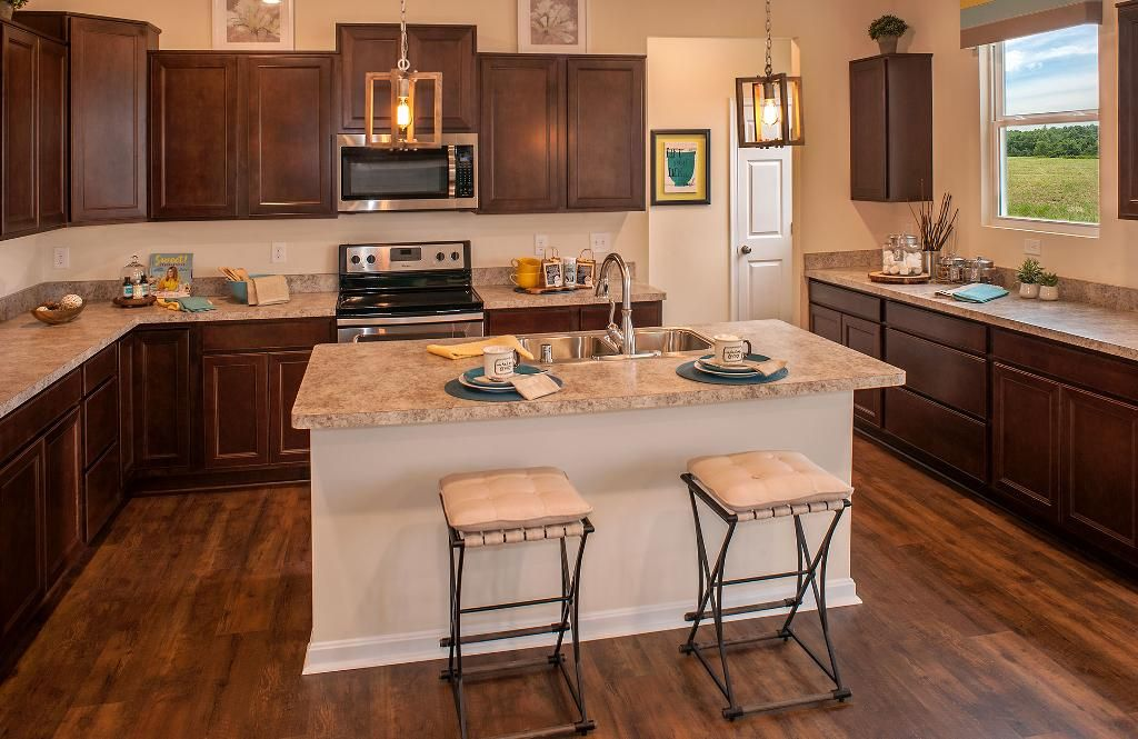 kitchen with dark cabinets, an island and wood floors; the ashton