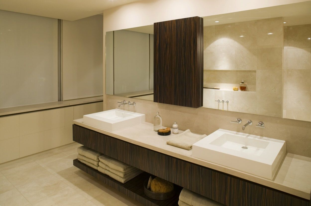 Double white sinks with dark brown vanity and storage bathroom
