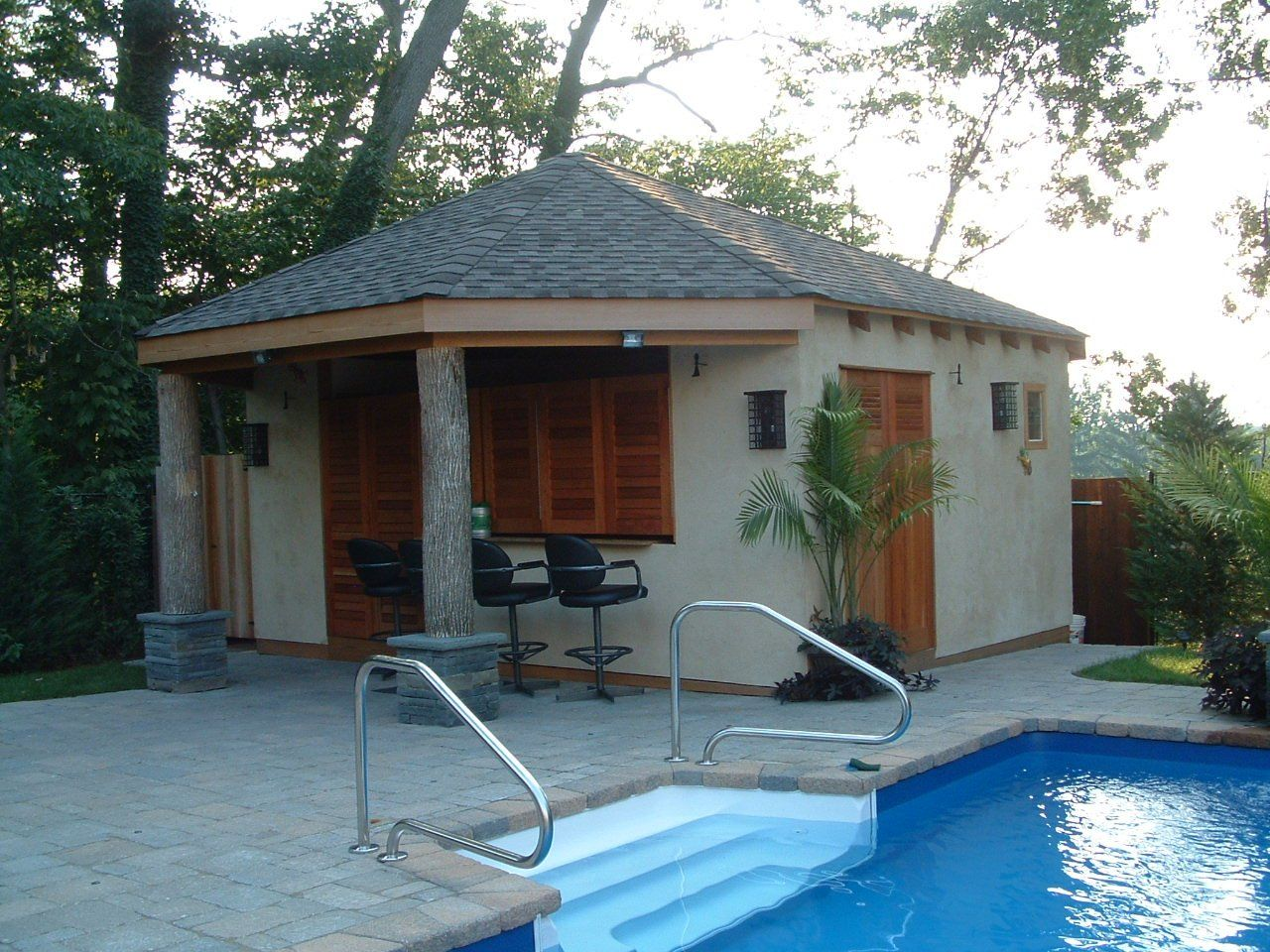 Operable Louvered Exterior Shutters Used To Enclose A Pool