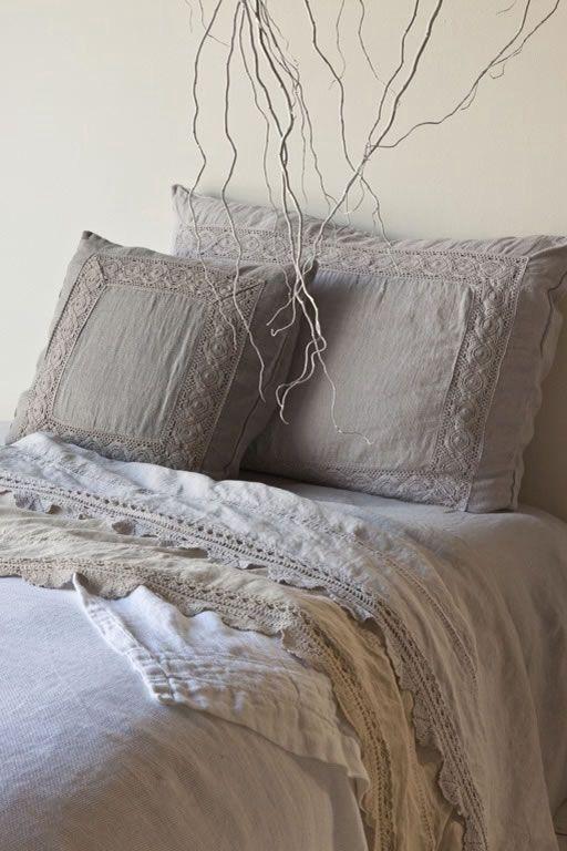Detalle de un dormitorio con cama tapizada y mesitas \