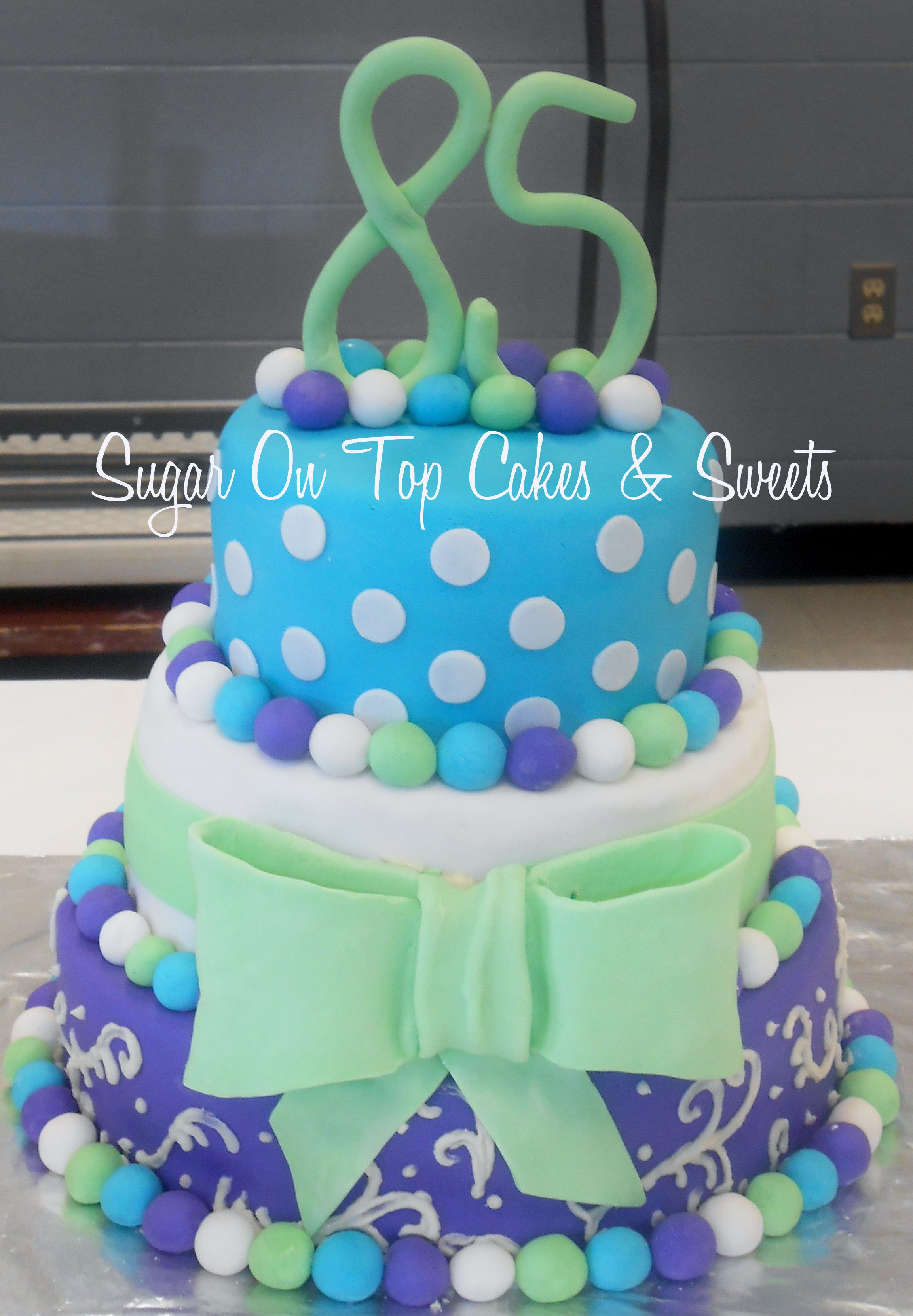 3 tier turquoise green and purple birthday cake with polka dots