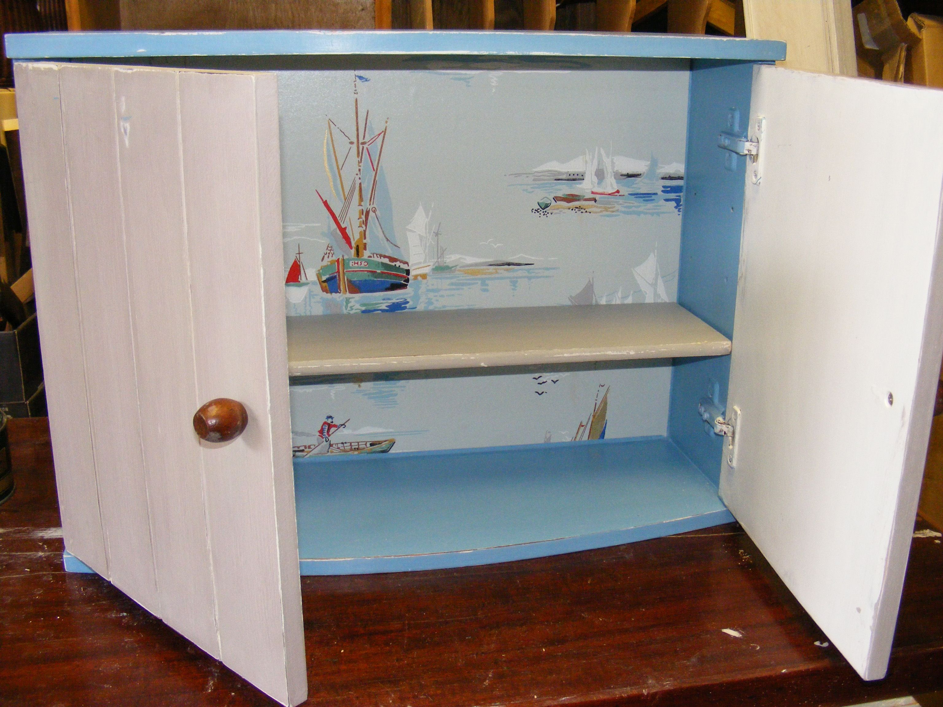 Repainted dark wood bathroom cabinet. Chose boat themed vintage wall paper to hide inside. I would hang this in my beach hut if I had one. I made this on a rainy day 17 miles from the nearest beach. (Charmouth)