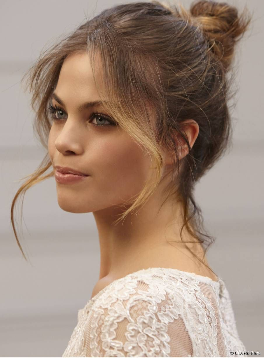 Messy Bun Updo When Styling An Updo With A Heart Shaped Face Keep A Few Face Framing Pieces Loose To Sof Face Shape Hairstyles Face Framing Hair Hair Styles
