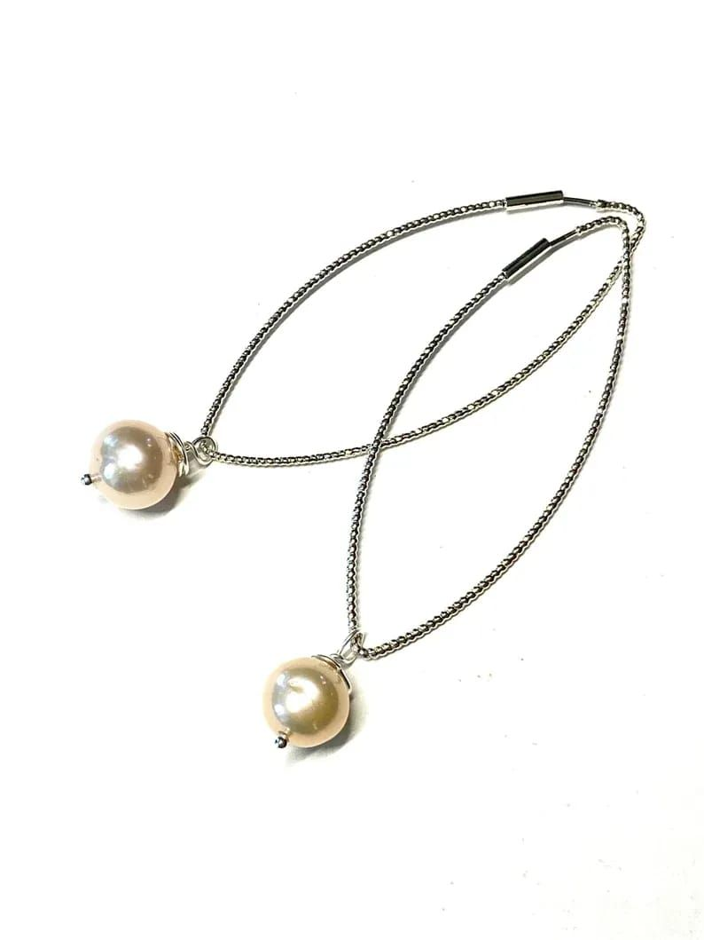 Pearls are always glamorous especially if they're big and dramatic! Hang these long beauties on your ears for your next fancy event and wait for the compliments to roll in. The coloring of the pearls are a lovely vintage style. The pearls are 11mm. And they're suspended on metal diamond forms. At