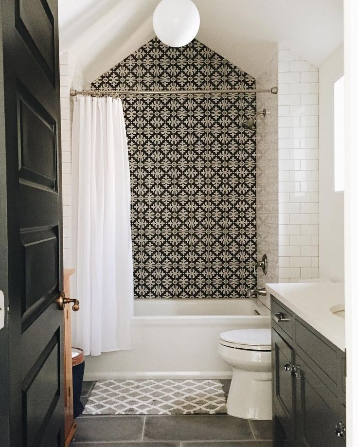 Printed backsplash, black bathroom door, tile bathroom floor, green cabinets, na… Banyo
