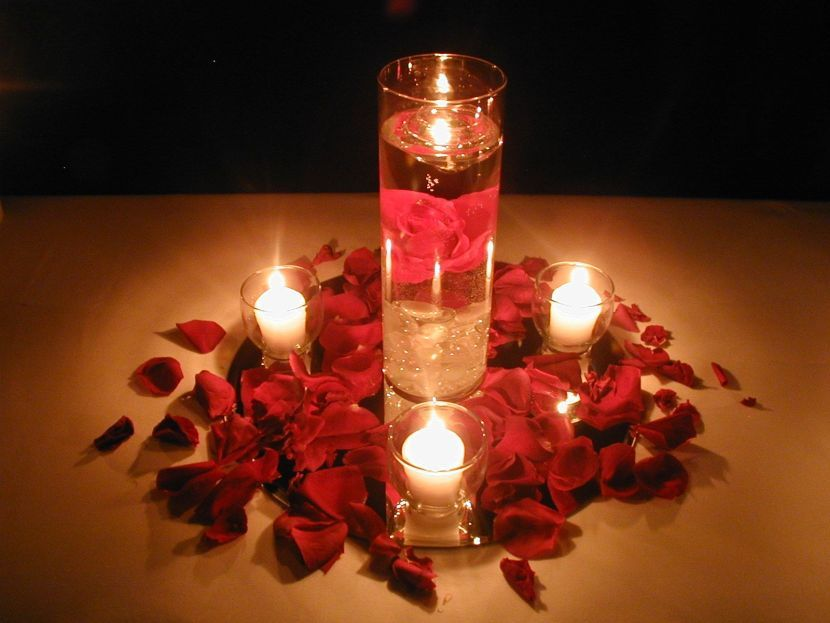Candles decorated in glass with red rose petals as table ...