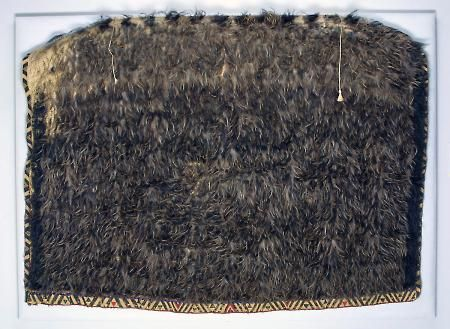 """This feather cloak was worn by renowned Māori chief Mita Taupopoki (ca. 1845–1935) during a tour of Australia, the United States, and England in 1910–1911.f Hand-woven from flax fiber and covered with kiwi bird feathers, this cloak is called a kakahu kiwi. According to Hape, the taniko side border """"is a decorative Māori weaving technique used to create geometric patterns.""""  These labor-intensive cloaks were often considered personal taonga, or treasures."""