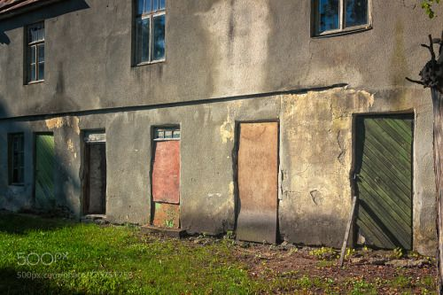 Five Doors Of An Abandoned Building by JukkaHeinovirta  red travel door old architecture building grass green wall shadows abandoned windows wooden no peopl