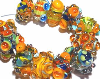 Included are 11 lampwork beads handmade by me in my studio.  These beads are made with lime, pinks, black and white. These are cool and pretty beads, with silver spots, plunged eyes, and encased cores. Would make a wonderful necklace, or what about a chunky bracelet? Very Glam!  The beads are about 10mmx 16mm The hole size is 3/32 Made from Moretti Glass.  I combine shipping for any amount paid for at the same time. Kiln annealed for strength and durability.  Thanks for looking