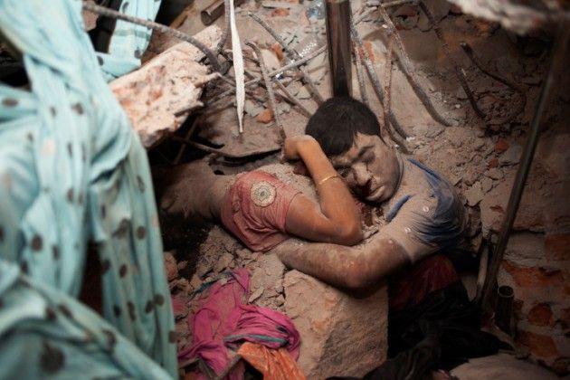 Taslima Akhter. Savar Dhaka, Bangladesh. Abril 24, 2013. Un edificio comercial de ocho pisos se colapsó debido a fallas estructurales. Una pareja se abraza. La parte baja de sus cuerpos se halla atrapada bajo el concreto. Una línea de sangre baja como lágrima del ojo del hombre.