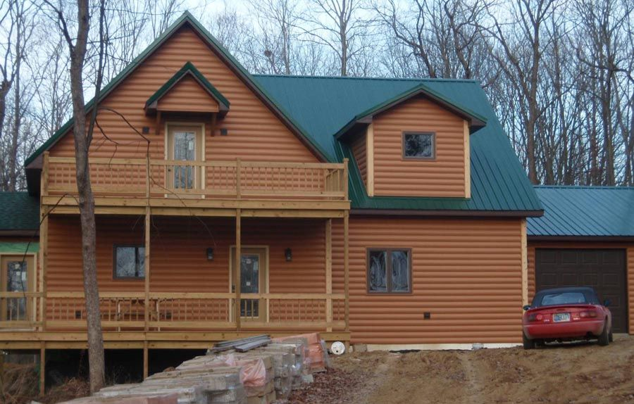 Vinyl Log Siding With Green Metal Roofing