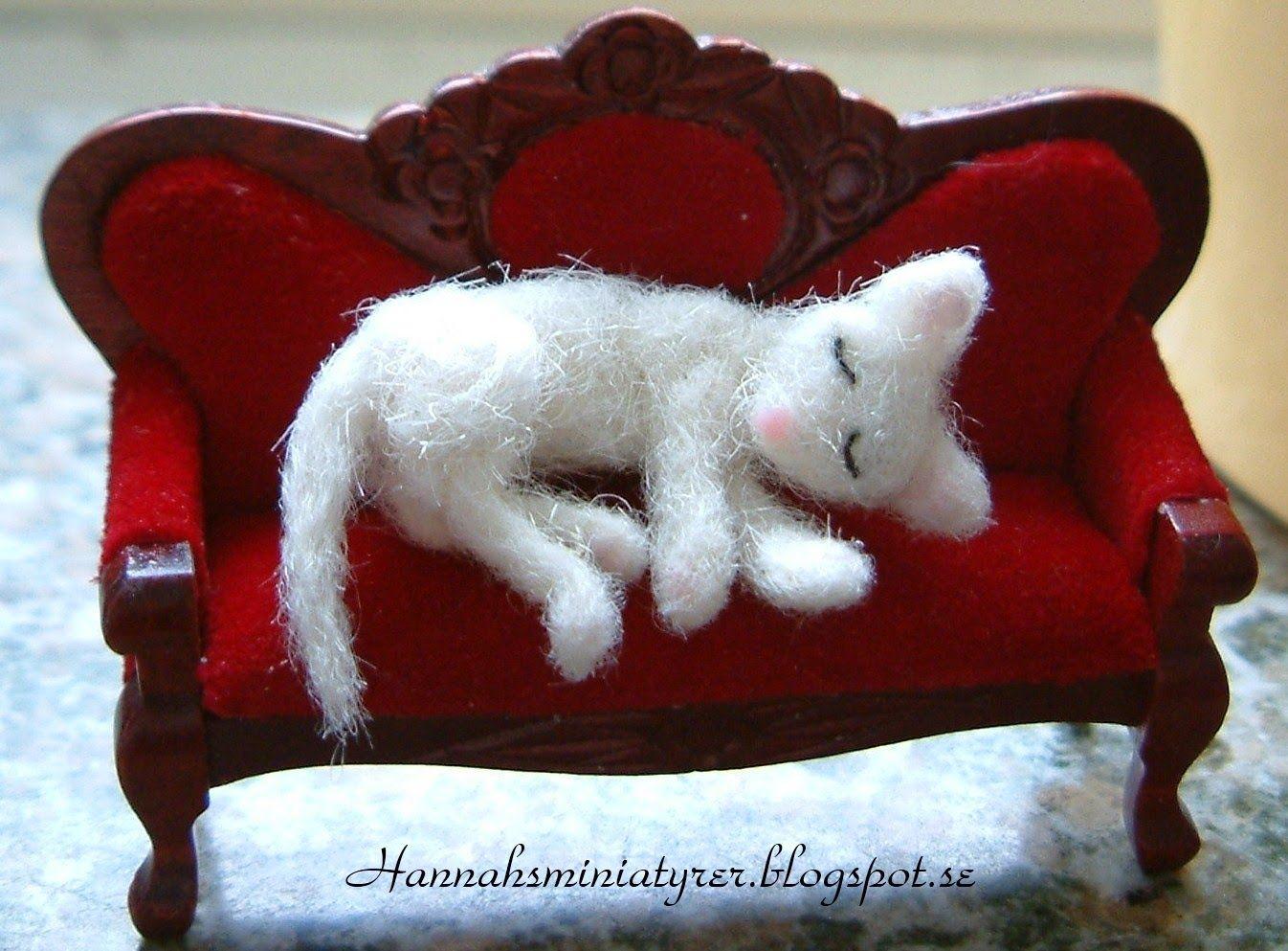 Hannahsminiatyrer: Needle felted cat on a sofa.