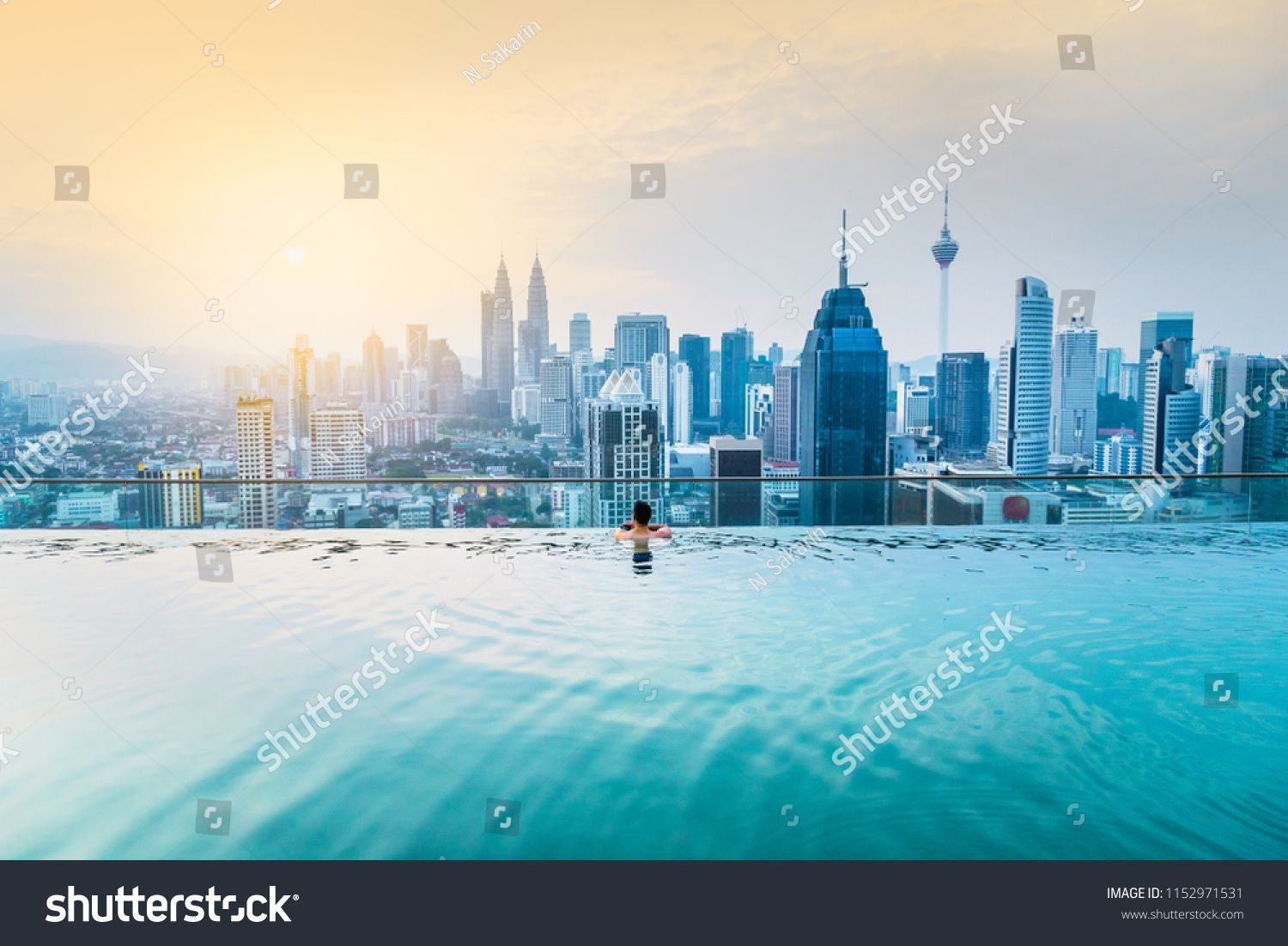 Asian Businessman Relax In Swimming Pool On Roof Top Behind