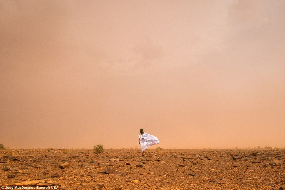 A Mauritanian man walking through a sand storm in the Sahara desert. Photo was taken between October and November in 2015