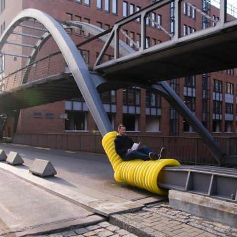 """Oliver Show's """"Street Furniture"""" series wraps yellow drainage pipes around public infrastructure in Hamburg, Germany"""
