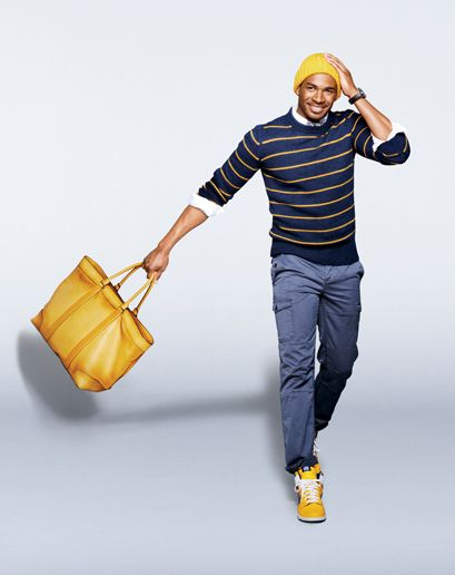 Damon Wayans JR in Hat, $45 by Gant Rugger. Bag, $658 by Coach Men's. Sneakers, $85 by Nike. Sweater by Closed. Shirt by Saturdays NYC. Tie by Prada. Pants by Boss Orange. Watch by Oris.