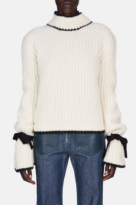 """There needs to be tension in the garments to make them feel more real, less precious,"" says Jonathan Anderson. For pre-fall 2016, the designer found that contrast in a chunky, fisherman-knit alpaca blend softened by belled sleeves that are cinched by attached grosgrain ribbon ties. Other striking details of this sweater include dropped shoulder seams and contrast tipping at the mock turtleneck, hem, and cuffs."
