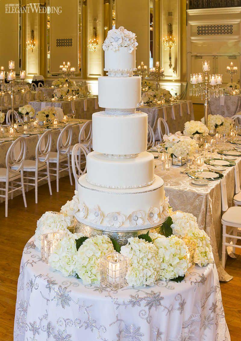 An Elegant White Wedding Reception Wedding Cake Table