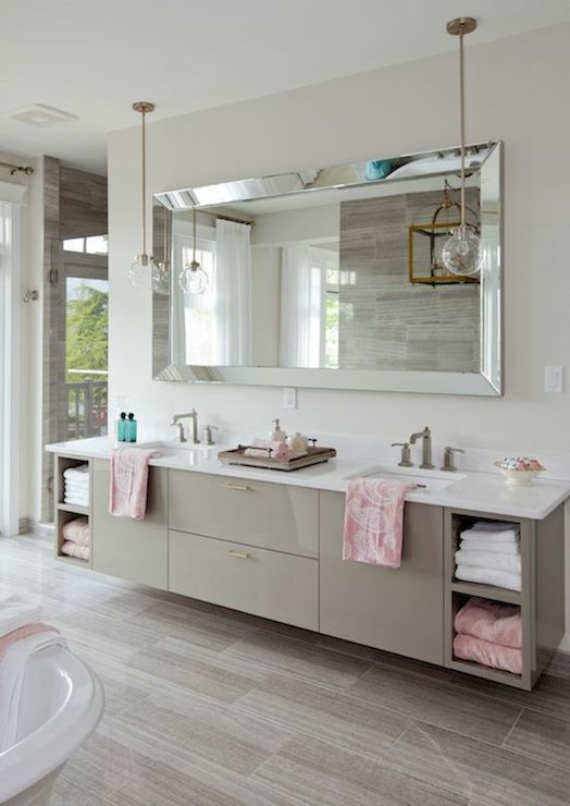 stunning bathroom featuring a floating gray double vanity with a white quartz countertop accented with pink towels as well as his and her sinks underneath a
