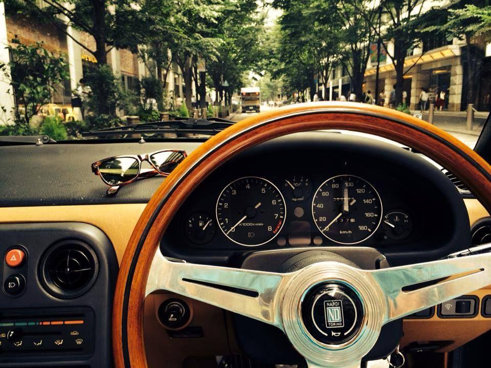 Miata MX-5 NA, Right hand drive, black & tan, with a Nardi wood grain steering wheel. Clean interior makes a clean feel.