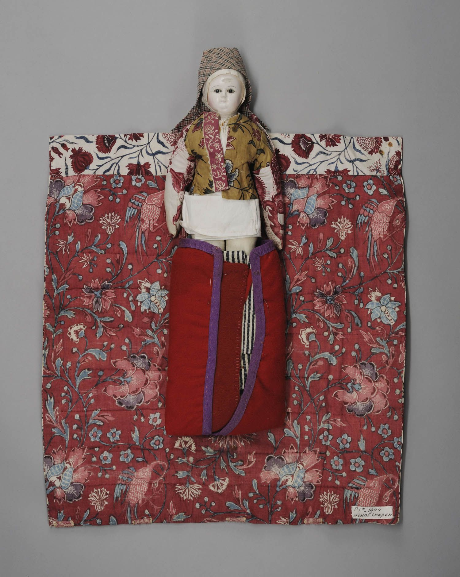 Doll dressed as a nurse in Hindeloopen, 1700-1800. The doll is dressed in Indian chintz clothes and wrapped in the same material, from the 18th century.