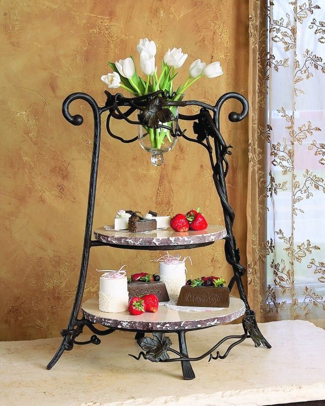 Bella Toscanca event server- Two Tiered marble boards adorned with a glass vase filled with florals.
