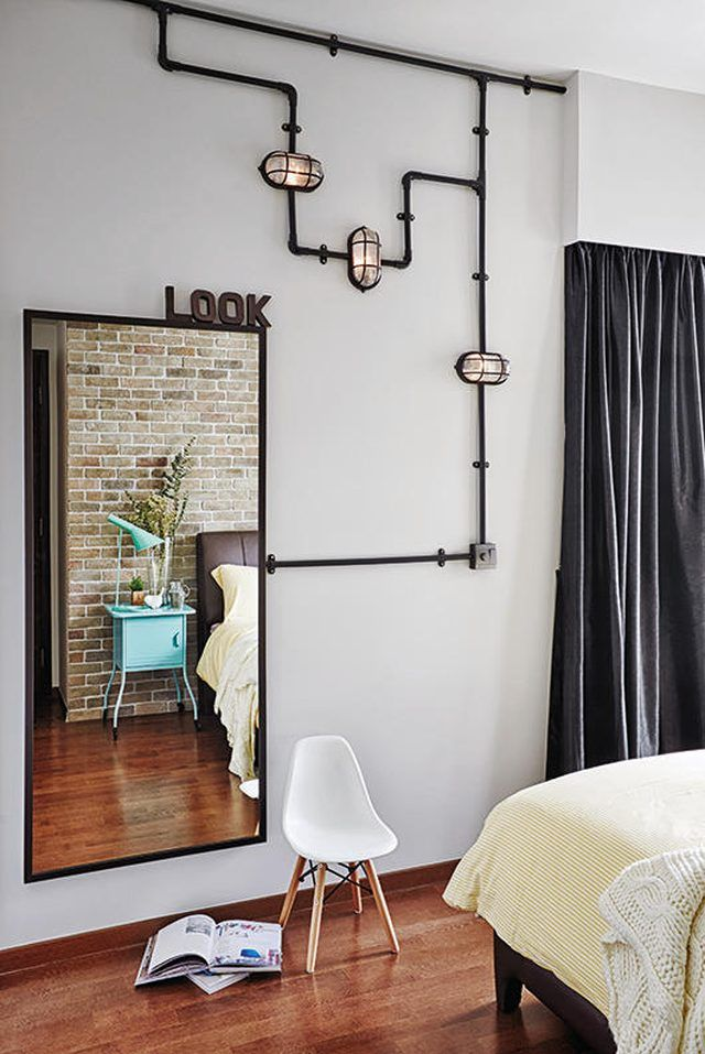 industrial bedroom with decorative pipe artwork running along wall