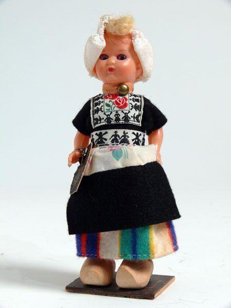 Eine blonde Frau in der Tracht von Volendam. Buntgestreifter Rock, schwarzer Bluse, Hose. Im Taillen- und Brustbereich ist auf die Bluse eine Stoffapplikation genäht mit schwarzes Muster auf weißem Grund, mit Windmühlen und Trachtenpärchen. Auf der Brust zusätzlich noch ein rotes Rosenmotiv. Unter dem gemusterten Gürtel im oberen Bereich der Schürze eine weiße Stoffapplikation mit einem violetten Blumenmuster. Weiße Leinenhaube mit Spitzen, Holzschuhe.  #NoordHolland #Volendam