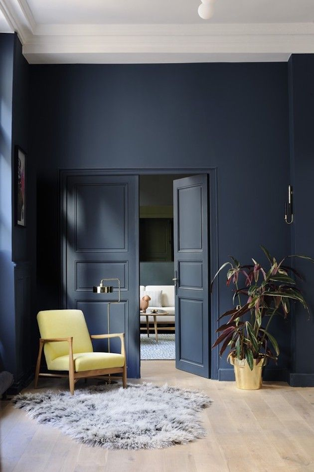 salon mur bleu marine fauteuil retro jaune