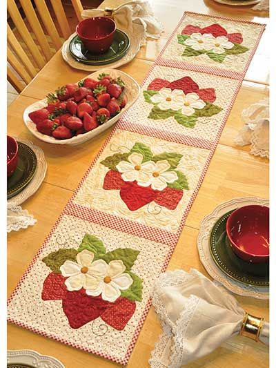 "Brighten up your table with these fun strawberries! You will love playing with your favorite red fabrics to create each of these yummy strawberries. Finished size is 12 1/2"" x 53""."