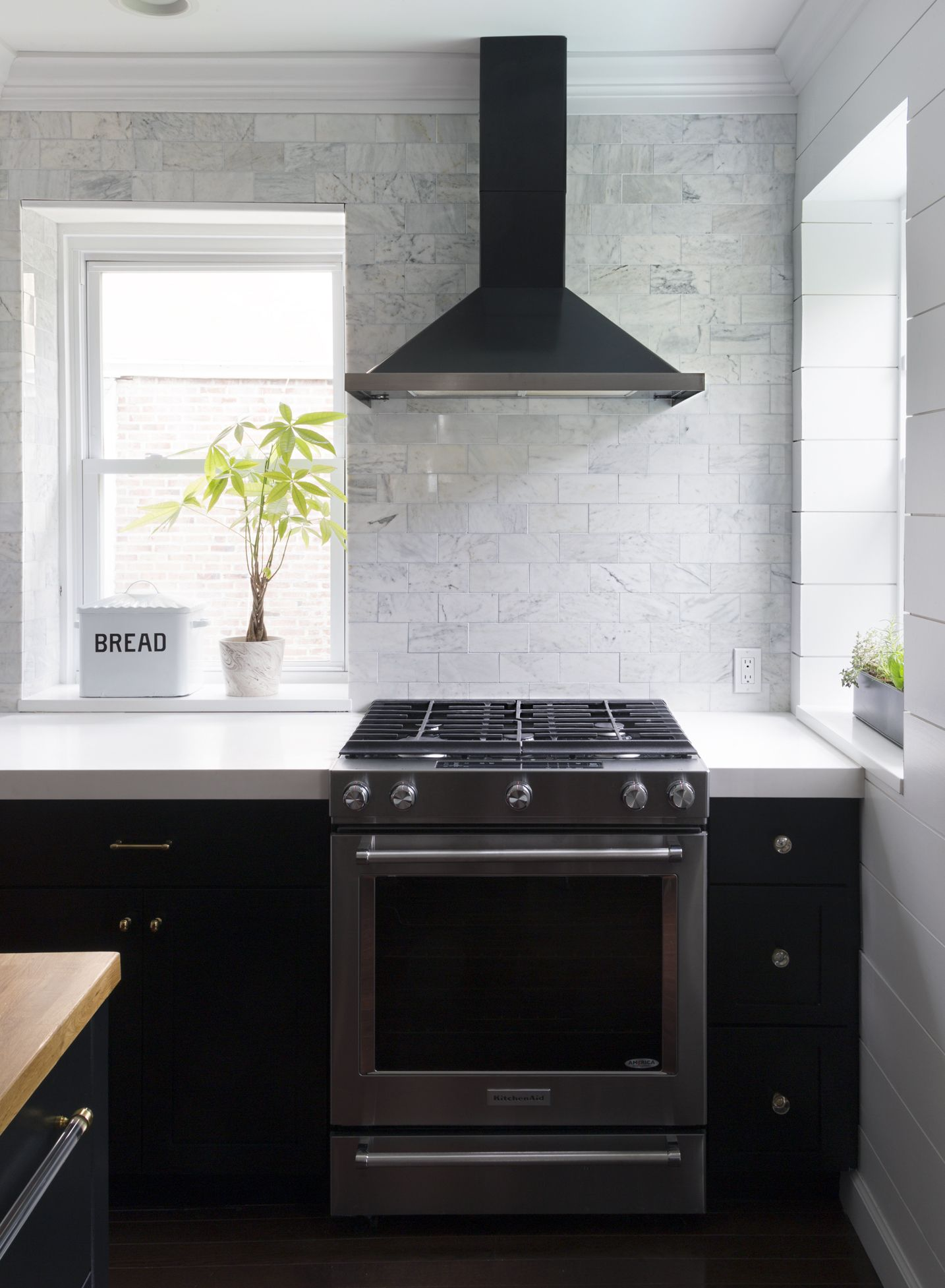 black kitchen with full wall of white marble tile black range hood