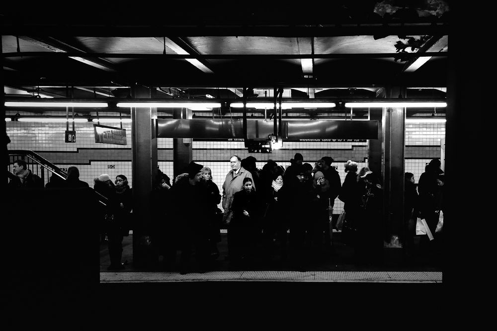 I shot this image in NYC Subway attracted by the man with the raincoat, being the only one wearing light colors on that platform while standing right under the light. Of course not all the others were wearing black, some were blue, some brown or dark grey, so I immediately figured out that editing the image in B&W he would pop out pretty sharply. The good addition, in my opinion, is that he looked at me exactly when I pressed the shutter, making the connection between me and him much stro...