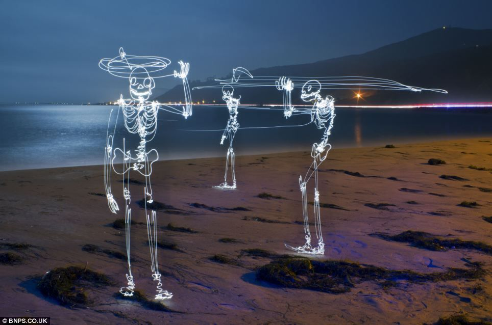 End of the world: Three skeletons wave goodbye in the dim light by an atmospheric windswept sea shore