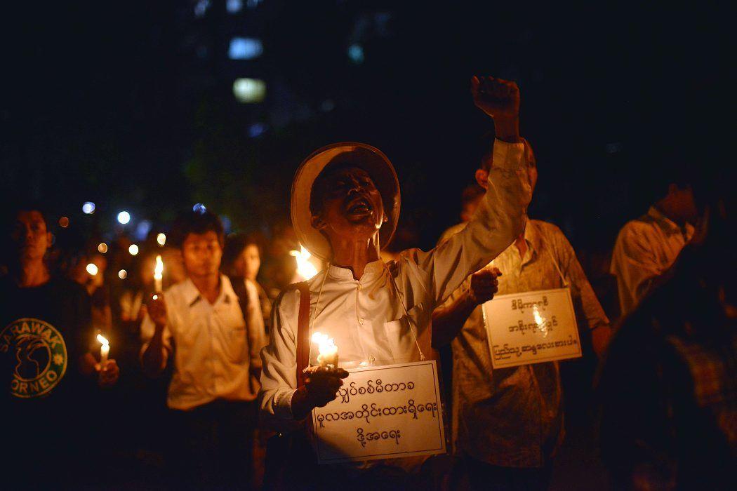 Manifestantes sostienen velas y gritan consignas mientras realizan una protesta contra los incrementos de precios en la electricidad en Yangon (Myanmar). (AFP/Ye Aung Thu/VANGUARDIA LIBERAL)