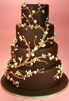 Caramel branches with delicate ivory sugar blooms encircle the tiers of this chocolate fondant-covered cake. Cake by Confetti Cakes